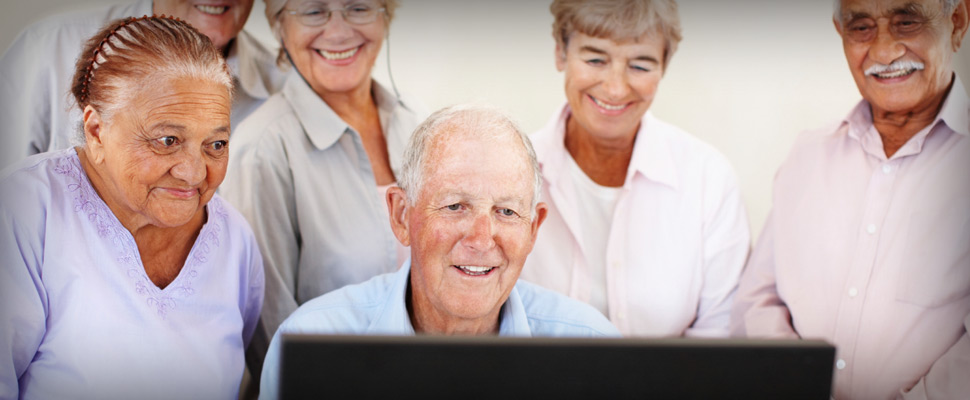 Elderly people around a computer